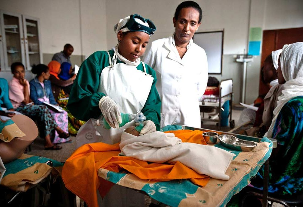 Midwife trainee practices newborn resuscitation on a doll as a supervisor looks on.