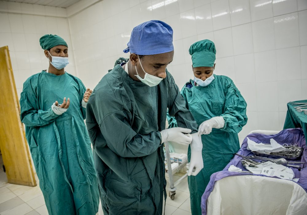 Three doctors preparing for surgery.