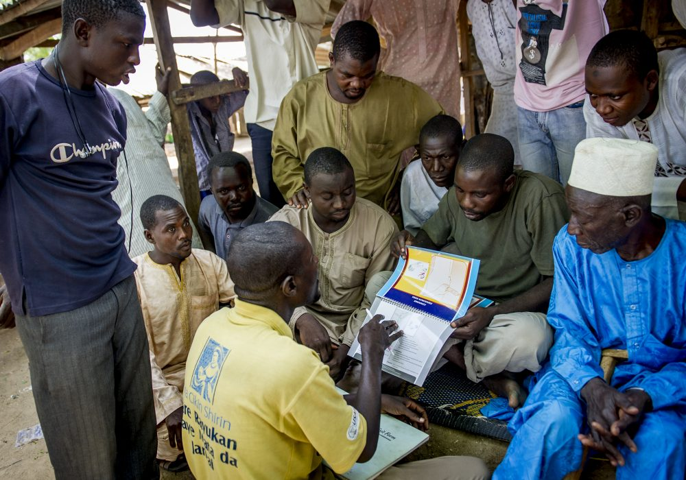 A male motivator uses a booklet to talk to a group of men about family planning.