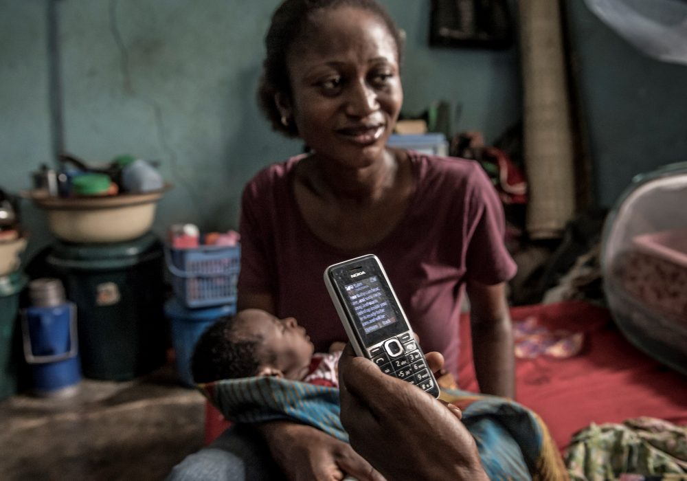A woman holds her baby as someone holds a cellphone with text.