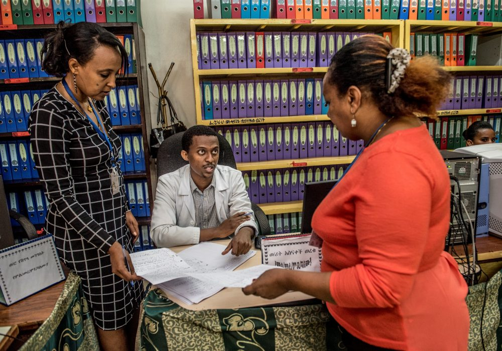 Two women holding papers and speaking to a man at a desk in a room with rows of binders..