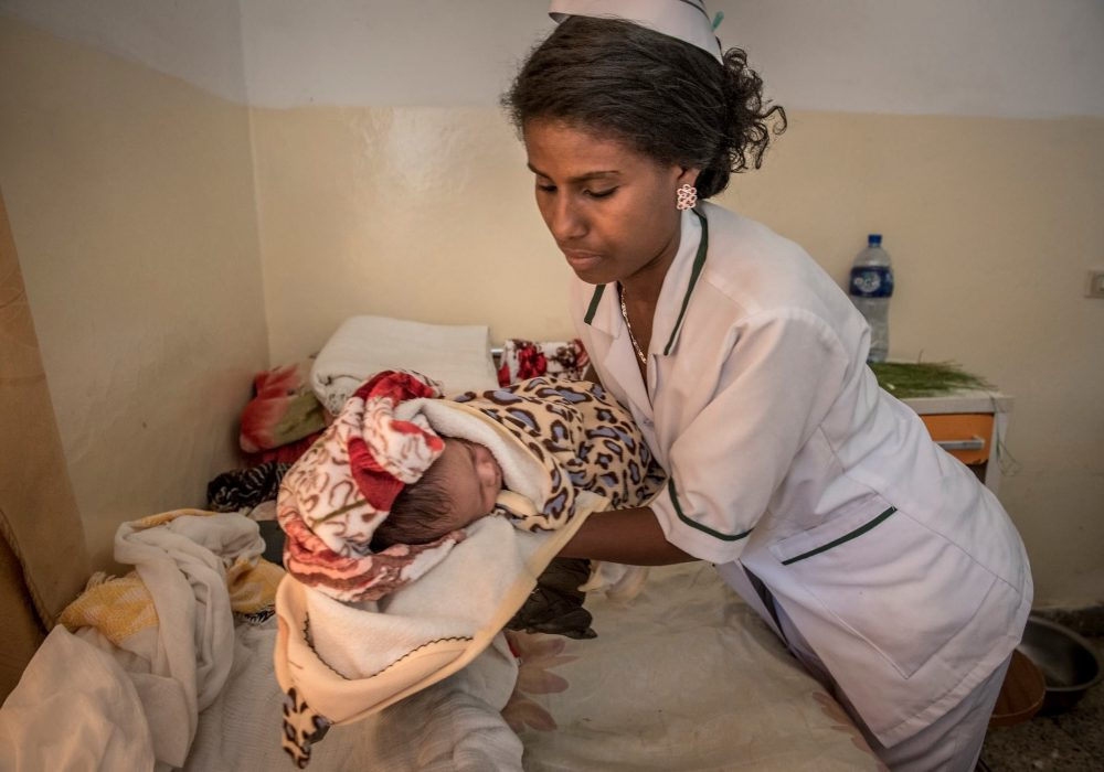 Midwife laying a newborn on a hospital bed.