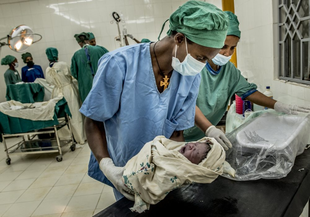 Doctor holding newborn for measurements