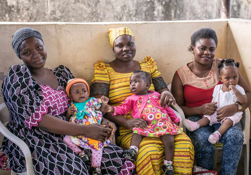 Three mothers sit with their babies