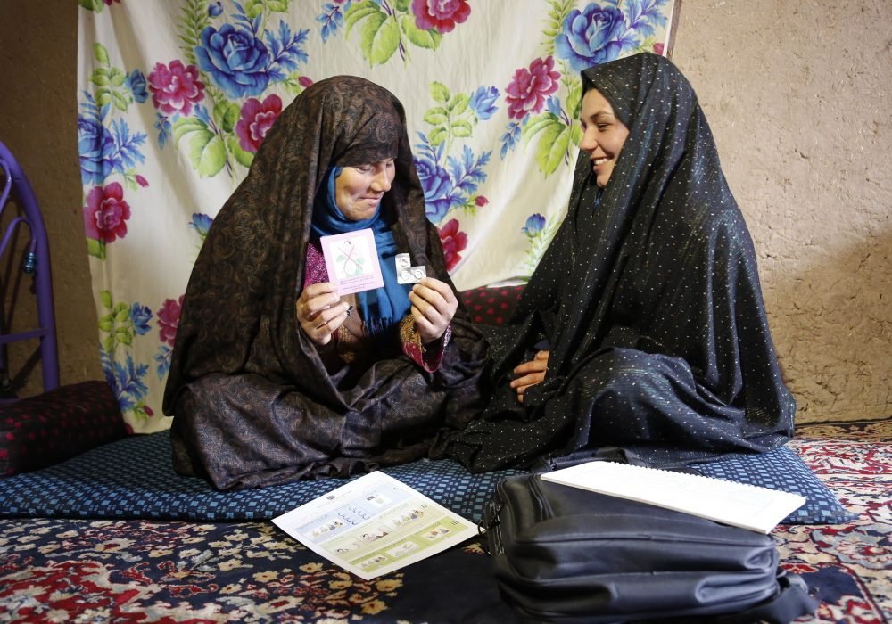Two women sitting on a rug. One hold an information cards and samples of misoprostol.